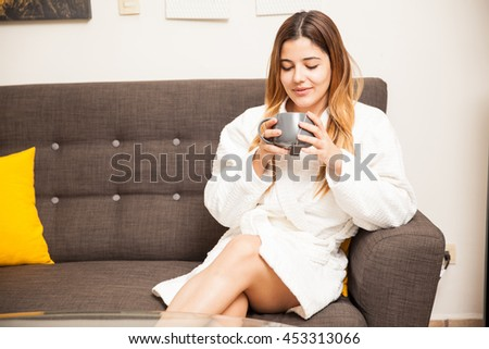 Beautiful young woman getting pampered in a spa and sitting in a waiting room while drinking some tea - stock photo