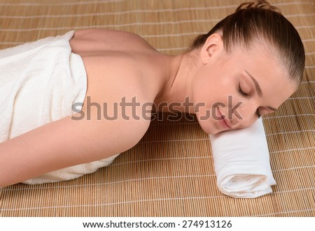 Beautiful young woman getting relaxing in the spa salon. Front view high resolution shot. Smiling model with closed eyes - stock photo