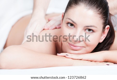 Beautiful young woman getting shoulder massage at spa - stock photo