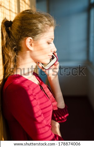 beautiful young woman girl with shadow from window blinds on chatting mobile cell phone - stock photo
