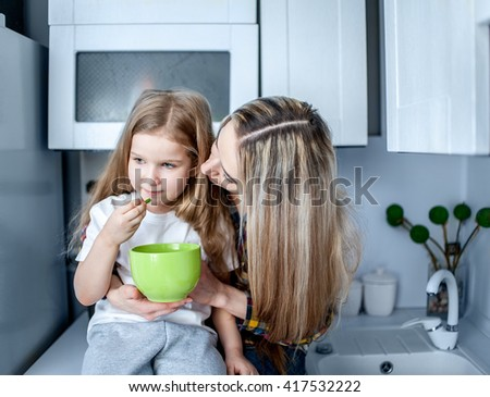 Beautiful young woman giving a child five years a pill in the kitchen  - stock photo