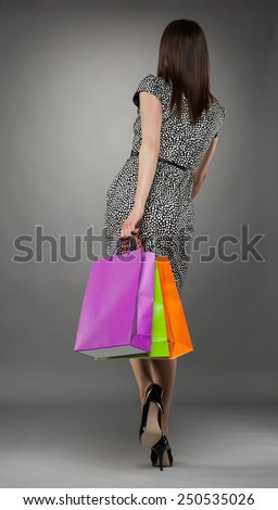 Beautiful young woman going with shopping bags, gray background - stock photo