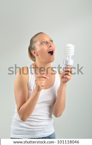Beautiful young woman having an idea with holding an energy-saving bulb - stock photo