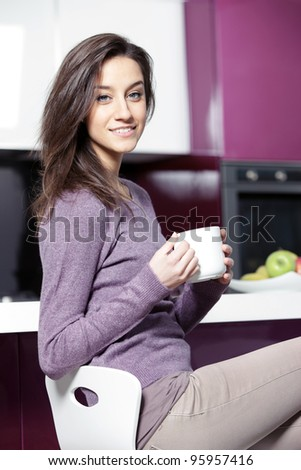 Beautiful young  woman having coffee while at the kitchen - stock photo