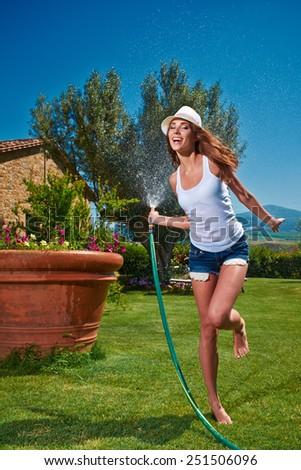 Beautiful young woman having fun in summer garden with garden hose splashing summer rain.  - stock photo