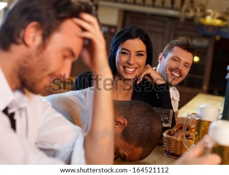 Beautiful young woman having fun with friends in pub. Looking at camera, laughing. - stock photo