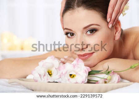 Beautiful young woman having massage in spa salon - stock photo