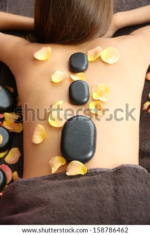 Beautiful young woman having stone massage in spa salon on color background - stock photo