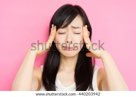 beautiful young woman having trouble against pink background - stock photo