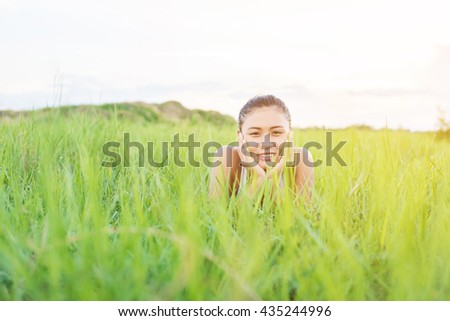 Beautiful Young Woman,Healthy Smiling woman Relaxing in Green Grass at meadows.
