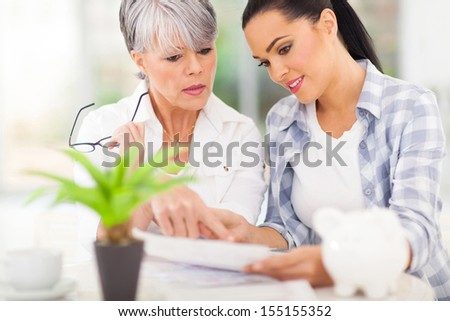 beautiful young woman helping her mother paying her bills - stock photo