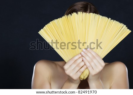 Beautiful young woman hidden behind a fan of spaghetti on a black background - stock photo