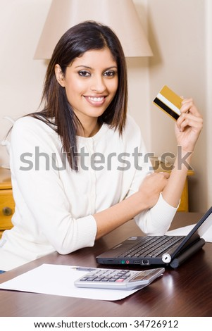 beautiful young woman holding a bank credit card and doing online shopping