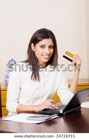 beautiful young woman holding a bank credit card and doing online shopping - stock photo