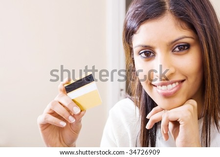 beautiful young woman holding a bank credit card and smiling - stock photo