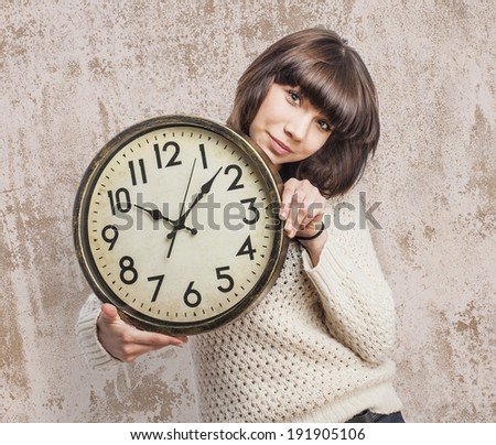 beautiful young woman holding a big clock