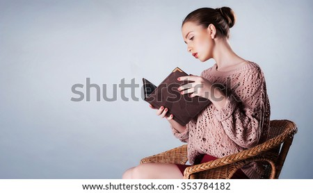 Beautiful young woman holding a book in her hands. High fashion look. Portrait of a fashionable model, perfect skin. Close up. Studio shot - stock photo