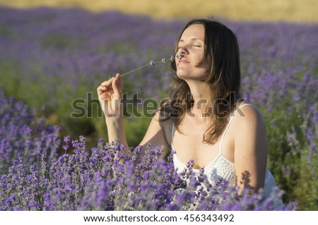 Beautiful young woman holding a bunch of lavender flowers enjoying their fragrance in the middle of a lavender field at sunset. - stock photo
