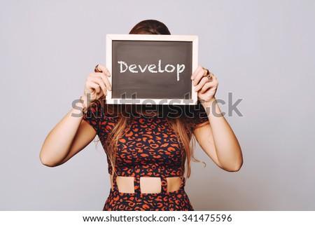 Beautiful young woman holding a chalkboard / blackboard saying develop. Caucasian young girl. - stock photo