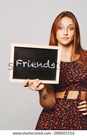 Beautiful young woman holding a chalkboard / blackboard saying friends. Caucasian young girl. - stock photo