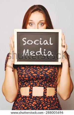 Beautiful young woman holding a chalkboard / blackboard saying social media. Caucasian young girl. - stock photo