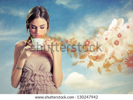 Beautiful young woman holding a cup of tea over a sky background, retro style - stock photo
