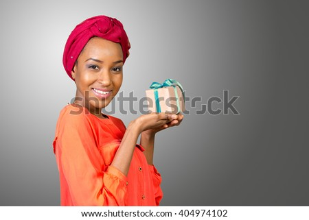 Beautiful young woman holding a gift - stock photo
