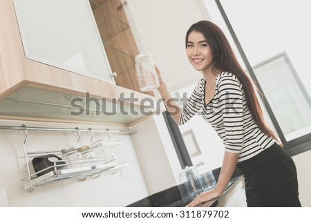 Beautiful young woman holding a glass in a modern kitchen, Noise and film grain toned image. - stock photo