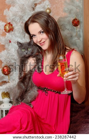 Beautiful young woman holding a glass of champagne and a black cat in front of a white Christmas tree. - stock photo