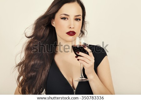 beautiful young woman holding a glass of red wine, studio white