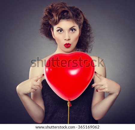 Beautiful young woman holding a  inflatable ball in the shape of a heart .