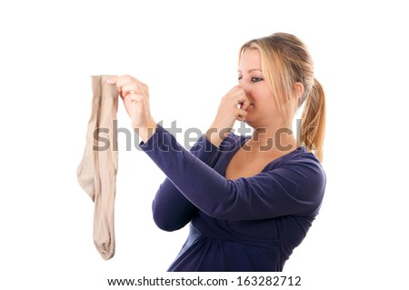 Beautiful young woman holding a man's sock. Isolated on white background.