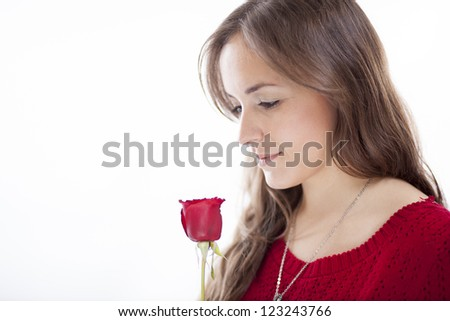 Beautiful young woman holding a red rose - stock photo