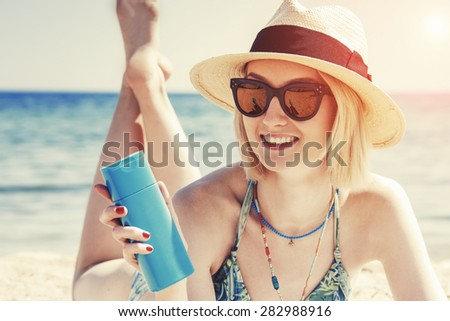 beautiful young woman holding a sun cream bottle on the beach - stock photo
