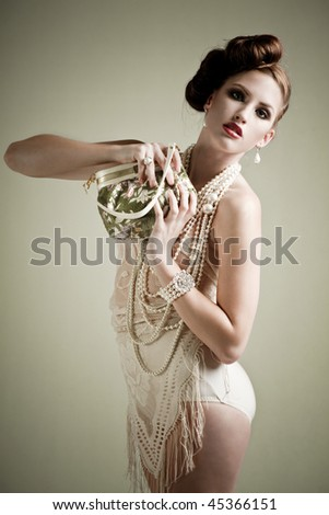 Beautiful young woman holding a vintage bag in a fashion portrait - stock photo
