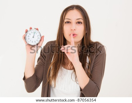 beautiful young woman holding alarm clock and hushing