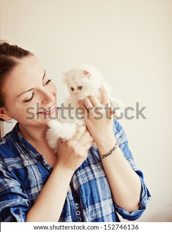 Beautiful young woman holding an adorable white Persian kitten - stock photo