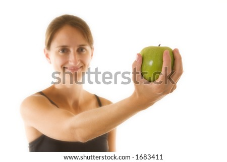 Beautiful young woman holding an apple - focus is on apple. - stock photo