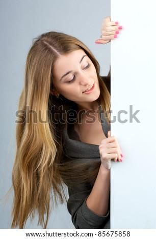 Beautiful young woman holding an empty billboard - stock photo
