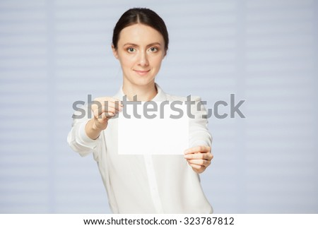 Beautiful young woman holding an empty sheet of paper, blue background