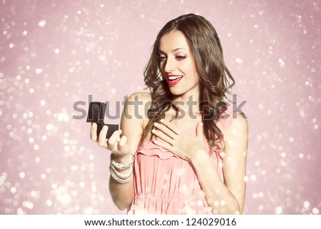 Beautiful young woman holding an open jewelery gift for anniversary. Pink glitter background. - stock photo