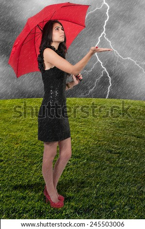 Beautiful young woman holding an umbrella in the rain - stock photo