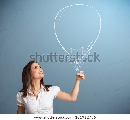 Beautiful young woman holding balloon drawing