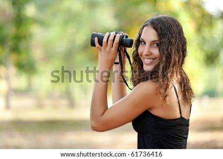 beautiful young woman holding binoculars and smiling at the camera