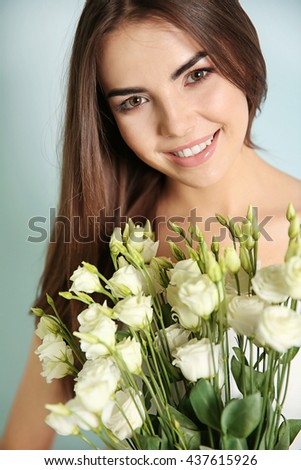 Beautiful young woman holding bouquet of white flowers, close-up