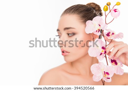 Beautiful young woman holding branch of orchid near her face - stock photo