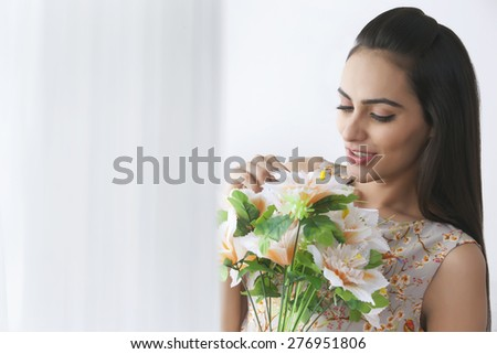 Beautiful young woman holding bunch of flowers