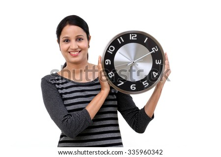 Beautiful young woman holding clock against white - stock photo