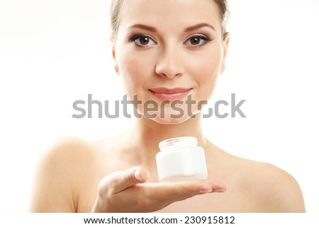 Beautiful young woman holding cream isolated on white - stock photo