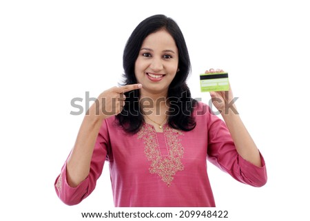 Beautiful young woman holding credit card against white background - stock photo